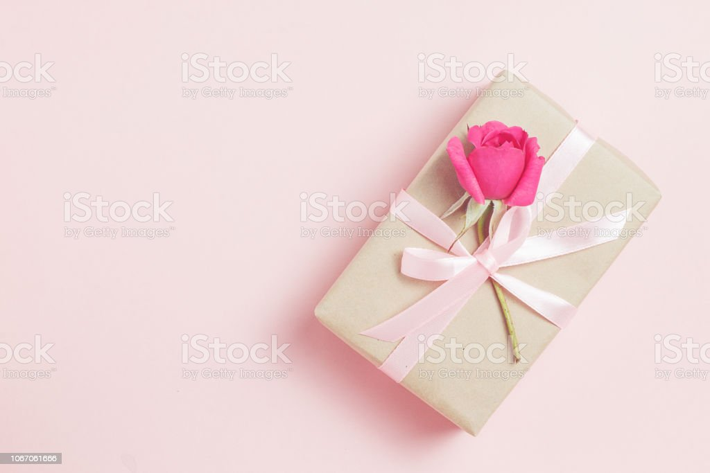 Gift box with rose on pink bacground. Vintage present. Gift box with pink ribbon and bow. Greeting card for Birthday, Womens or Mothers Day stock photo