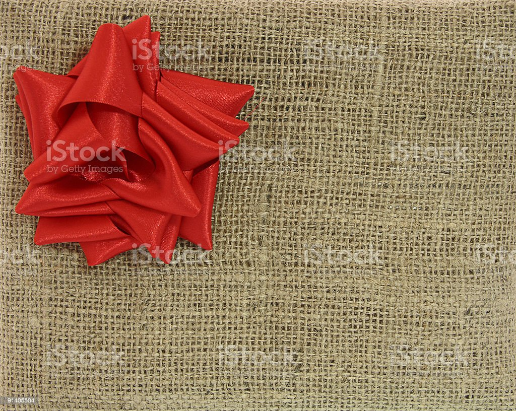 gift box wrapped by burlap canvas with satin red bow royalty-free stock photo