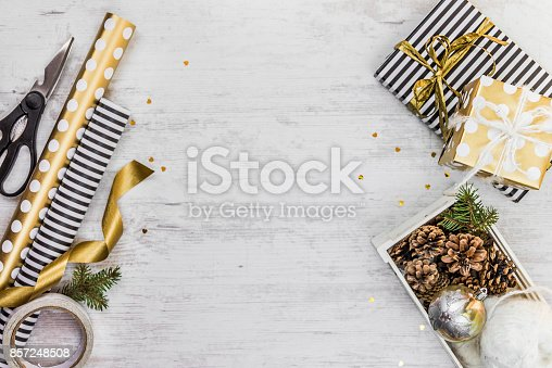 istock Gift box wrapped in black and white striped paper with golden ribbon, a crate full of pine cones and christmas toys and wrapping materials on a white wood old background. Christmas presents preparation. 857248508