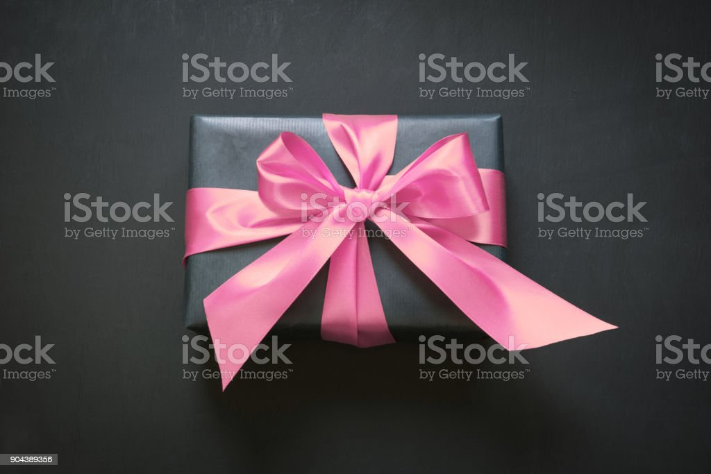 Gift box wrapped in black paper with pink ribbon on black surface. View from above. Copy space. stock photo