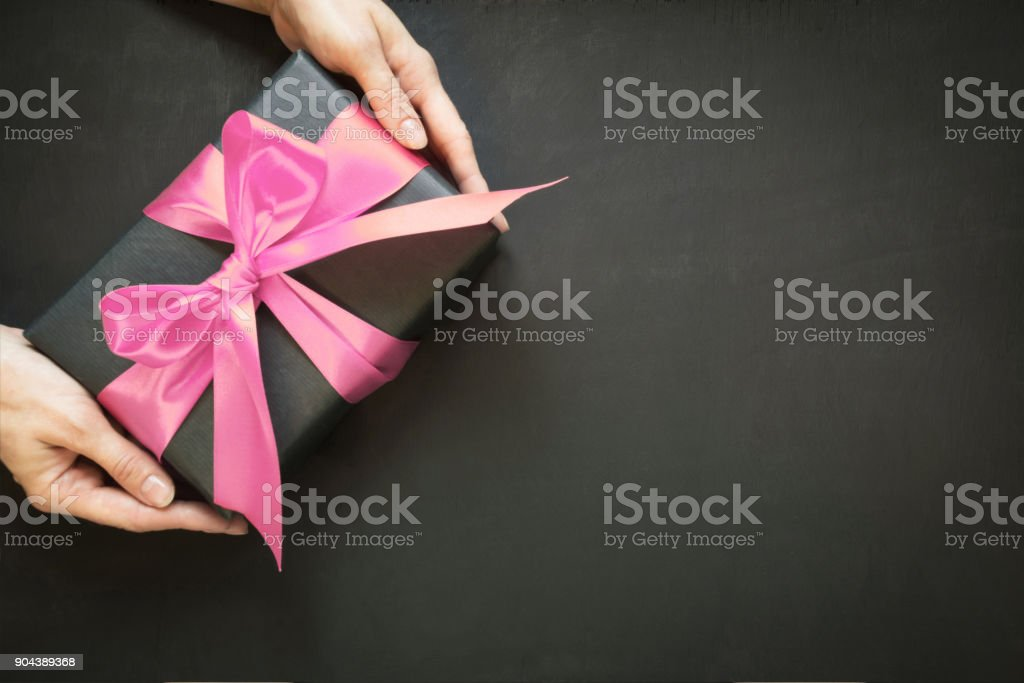 Gift box wrapped in black paper with pink satin ribbon in female hand on black surface. Copy space. View from above. stock photo