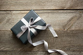 Gift box wrapped in black paper with ribbon on board.