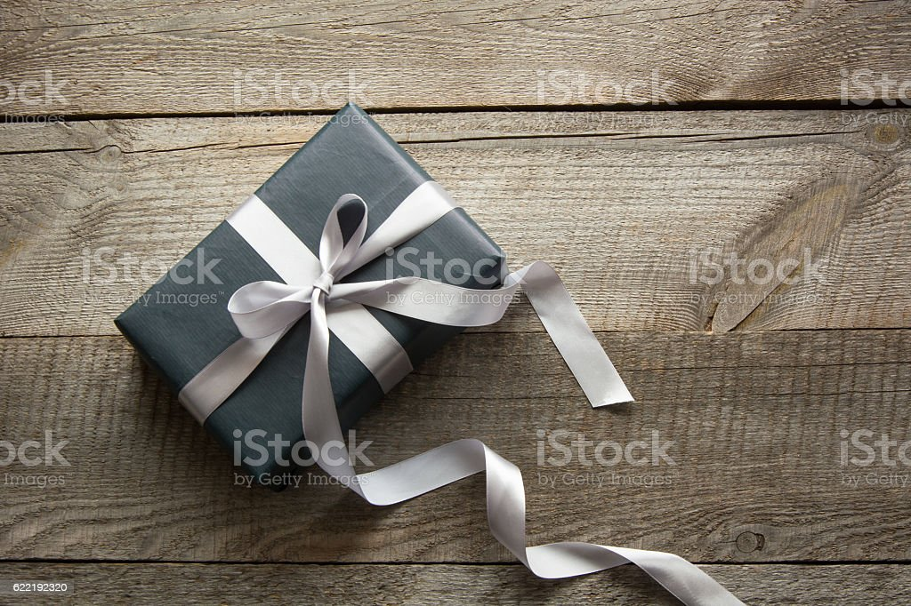 Gift box wrapped in black paper with ribbon on board. stock photo