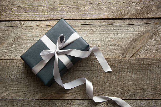 Gift box wrapped in black paper with ribbon on board. – Foto