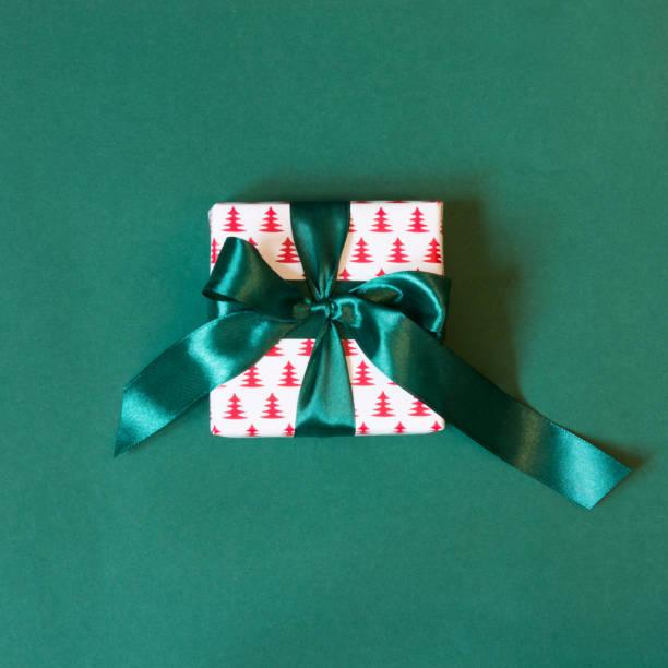 geschenkbox verpackt in designpapier mit grünen band auf grüne fläche. ansicht von oben. - gutschein weihnachten stock-fotos und bilder