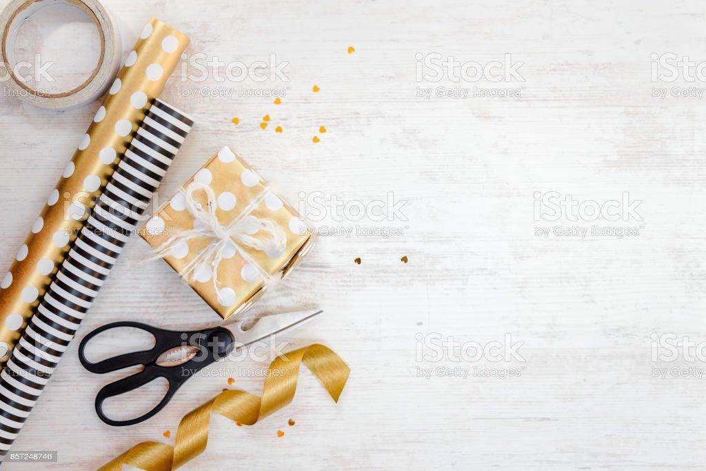 Hediye kutusu altın noktalı kağıt ve ambalaj malzemeleri bir beyaz tahta eski arka plan üzerinde sarılı. Boş alanı. stok fotoğrafı
