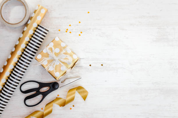 gift box wrapped in golden dotted paper and wrapping materials on a white wood old background. empty space. - wrapping paper stock photos and pictures