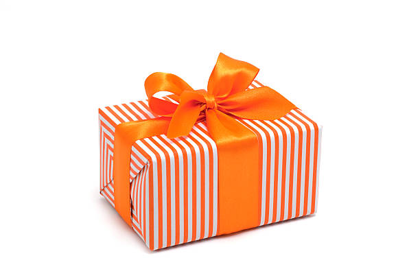 Gift box wrapped in orange stripped paper with an orange bow stock photo