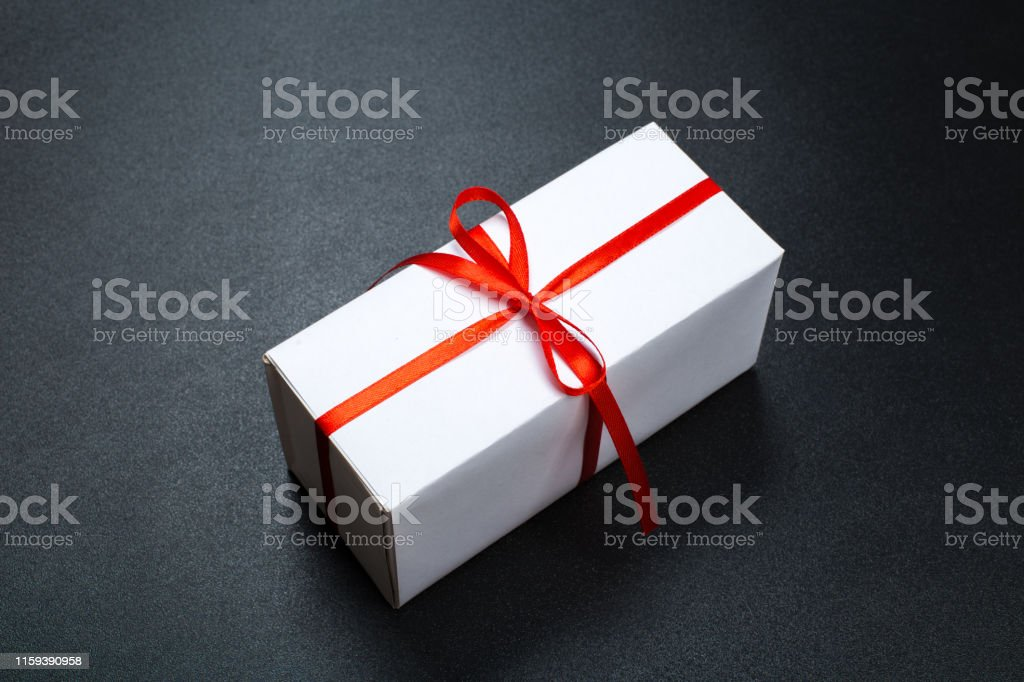 Gift box wrapped in paper with red ribbon on black surface. Top view