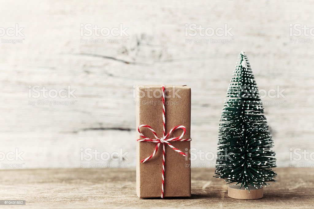 Gift box wrapped kraft paper and little decorative fir tree.