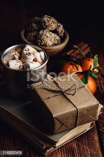 Gift box wrapped with craft paper. Rustic mug with hot chocolate and marshmallows.