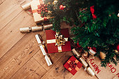 istock Gift boxes and Christmas crackers placed beside Christmas tree. 869386220