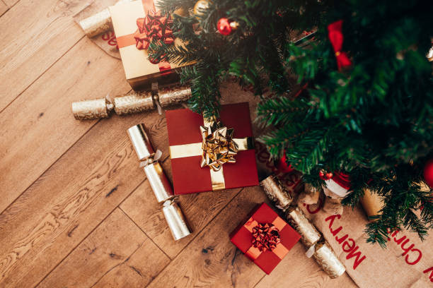 gift boxes and christmas crackers placed beside christmas tree. - christmas tree stock photos and pictures
