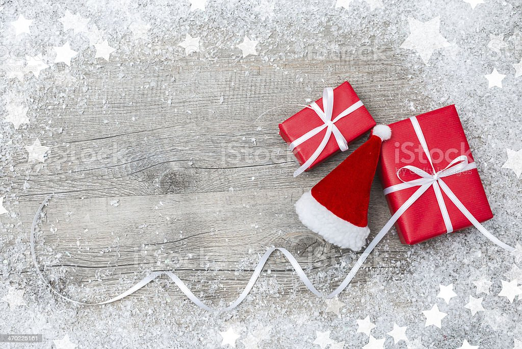 Gift boxes with bow and Santa hat on wooden background