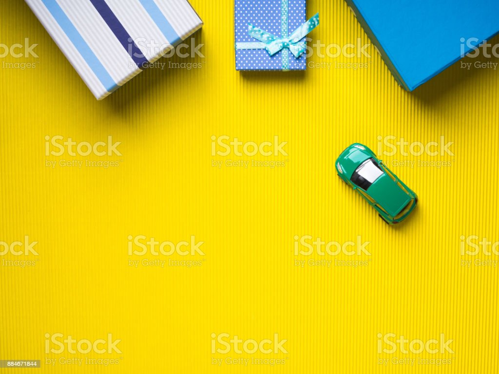 Gift boxes and toy car on yellow background Blue Gift boxes and a toy car on vibrant yellow background. Christmas fathers day shopping. Travelling car insurance purchase concept Backgrounds Stock Photo