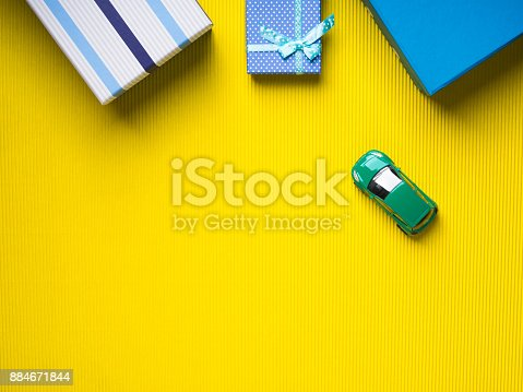istock Gift boxes and toy car on yellow background 884671844