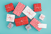 Gifts Collection wrapped in red and white paper with blank label forr a text on blue background.