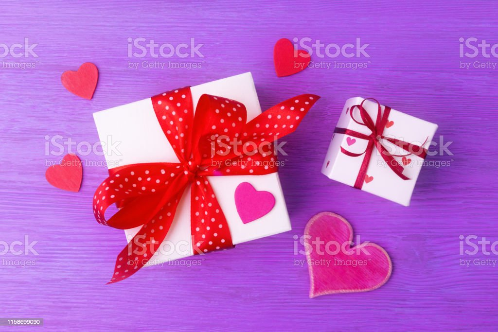 Gift boxes with red bows and hearts over violet wooden background