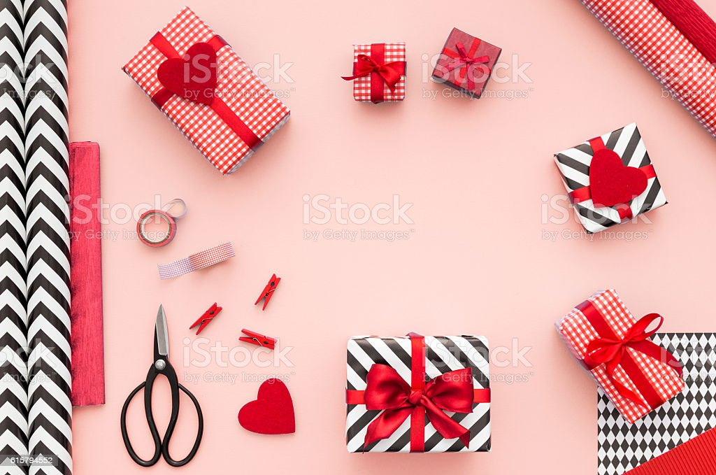 Gift boxes wrapped in red checked paper on pink background. Gift boxes wrapped in red checked paper and the contents of a workspace composed. Different objects on a pink color table. Flat lay.Christmas (xmas) or New year gift packing. Holiday decor concept. Above Stock Photo