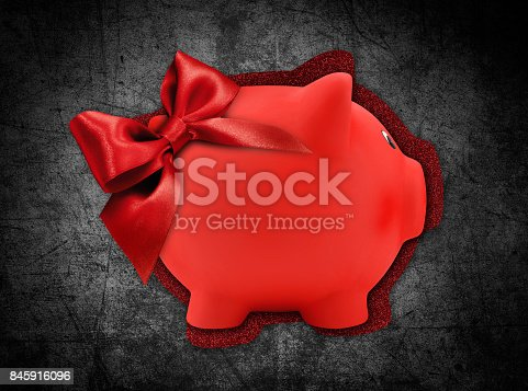 670414478 istock photo gift card label in the shape of a red piggy bank with red glitter ribbon bow isolated on black background 845916096