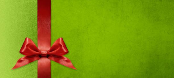 geschenk-karte wünscht frohe weihnachten hintergrund mit roten band schleife auf grün glänzend lebendige farbe textur vorlage mit leeren kopierraum - gutschein weihnachten stock-fotos und bilder