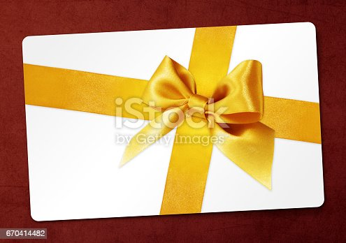 670414478 istock photo gift card with golden ribbon bow Isolated on red background 670414482