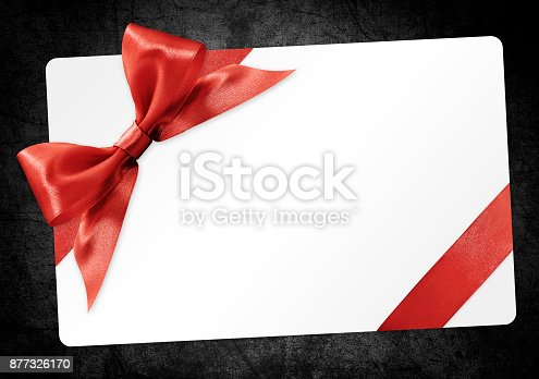 670414478 istock photo gift card with red ribbon bow Isolated on black grunge background 877326170