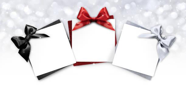 geschenkkarten mit schwarz, rot und silber band beugen isoliert auf weihnachten lichter hintergrund - günstige weihnachtsgeschenke stock-fotos und bilder