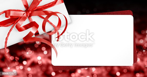 670414478 istock photo gift cards with red ribbon bow Isolated on christmas bright lights background 886672572