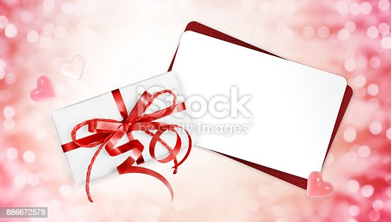 670414478 istock photo gift cards with red ribbon bow Isolated on christmas bright lights background 886672578