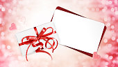 gift cards with red ribbon bow Isolated on christmas bright lights background