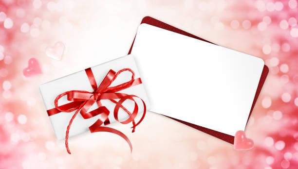 geschenkkarten mit roter schleife isoliert auf weihnachten lichter hintergrund - gutschein weihnachten stock-fotos und bilder