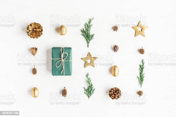 Photo of Gift, christmas decoration, cypress branches, pine cones. Flat lay