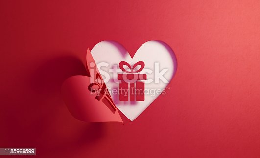 Gift box icon inside of a red folding heart shape on white background. Horizontal composition with  copy space. Gift concept.
