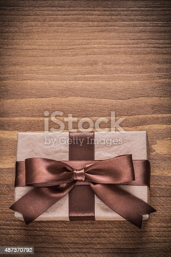 Gift container with brown ribbon on vintage wooden board copyspace.