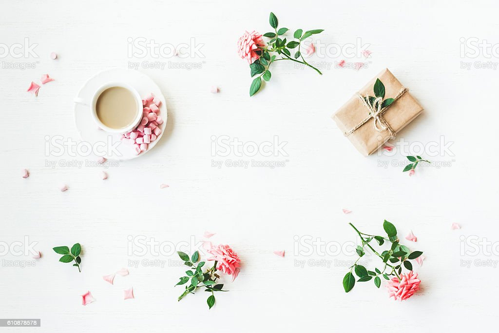 Gift, cup of coffee and rose flowers. Flat lay