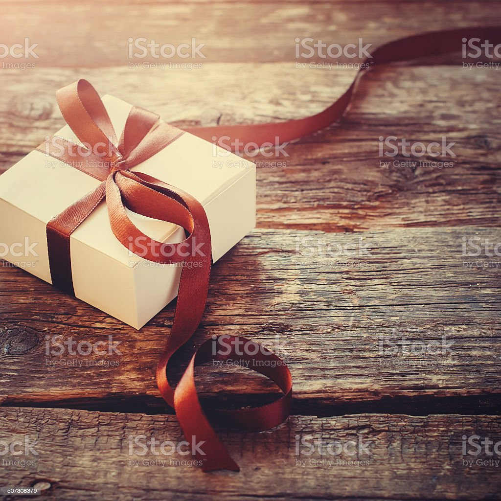 Gift Festive Box Brown Ribbon on Wooden Background stock photo