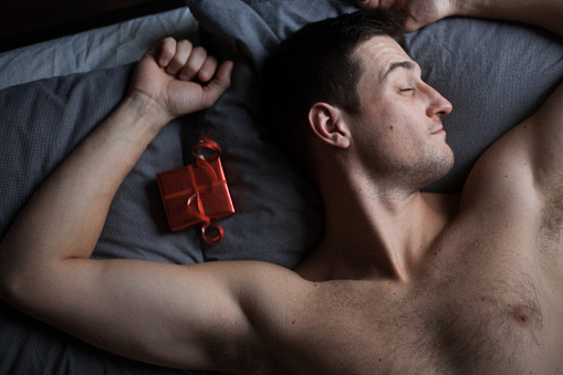 Sexy guy in bed on Valentine's Day morning