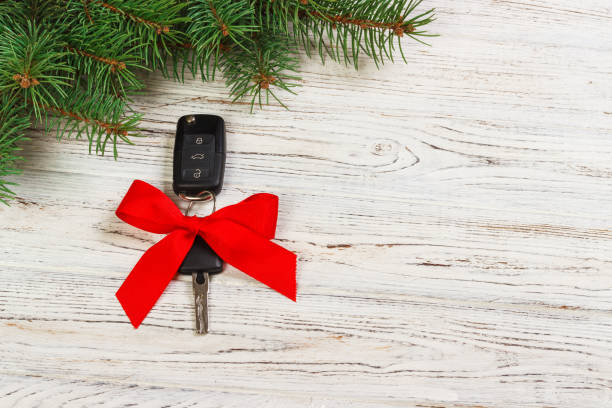 geschenk für weihnachten autoschlüssel. nahaufnahme von autoschlüsseln mit roter schleife als geschenk auf hölzernen hintergrund - autoschleifen stock-fotos und bilder