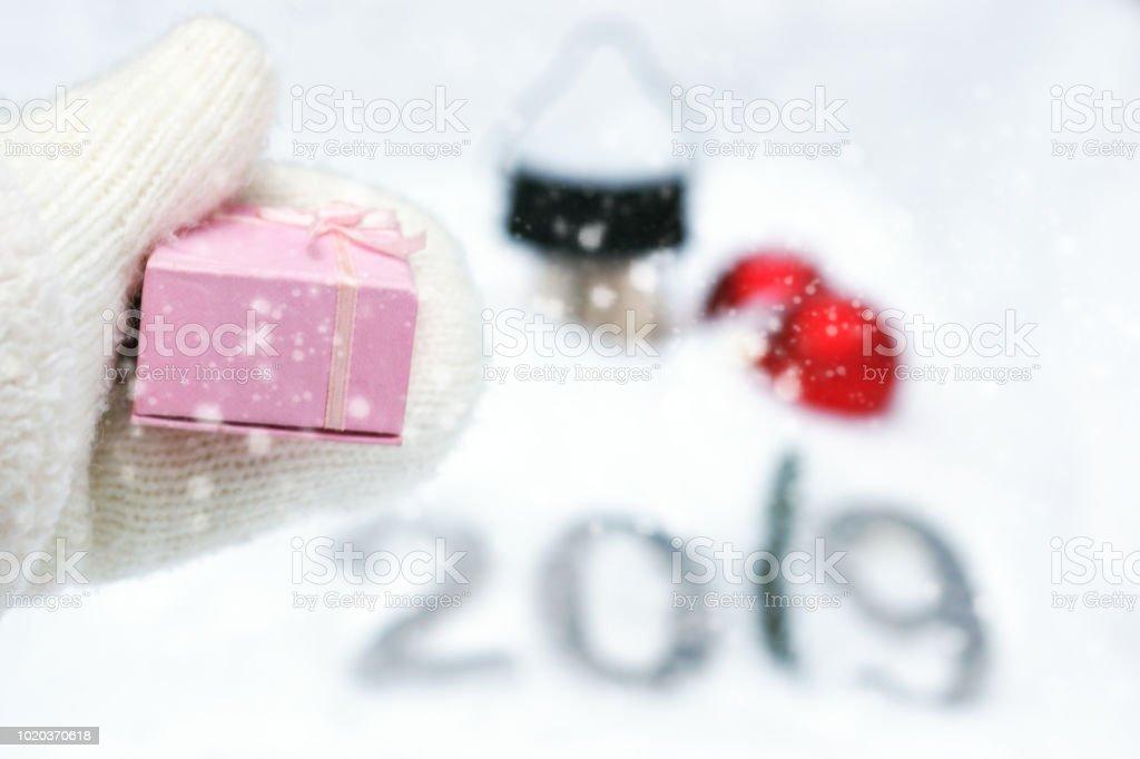 Un cadeau pour la nouvelle année 2019, un coup de main dans une mitaine tricotée blanche s'étend une boîte rose. - Photo