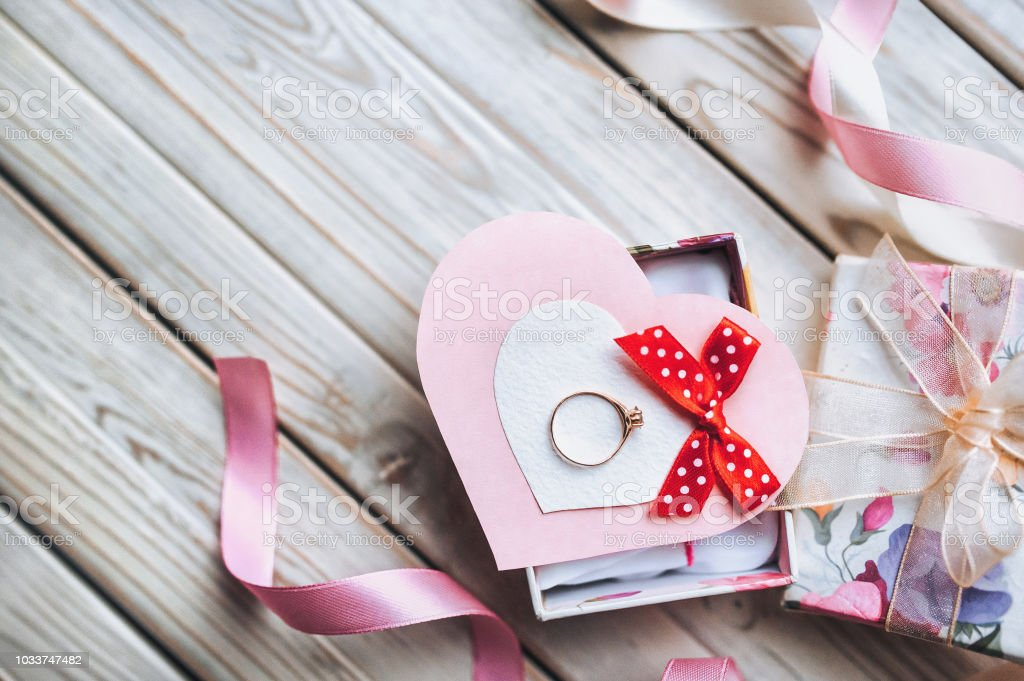 A gift for Valentine\'s Day. A wedding ring on a gift box with ribbons...