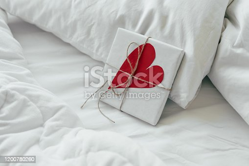 A gift box with a big paper heart lies in bed early in the morning. Content for honeymooners and lovers for Valentine's Day.