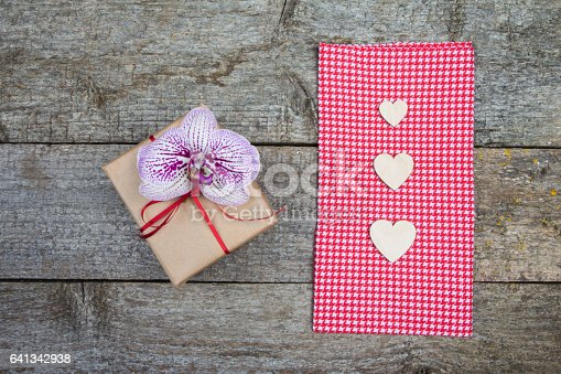 Gift for Valentine's Day, orchid flower and wooden hearts on a red napkin