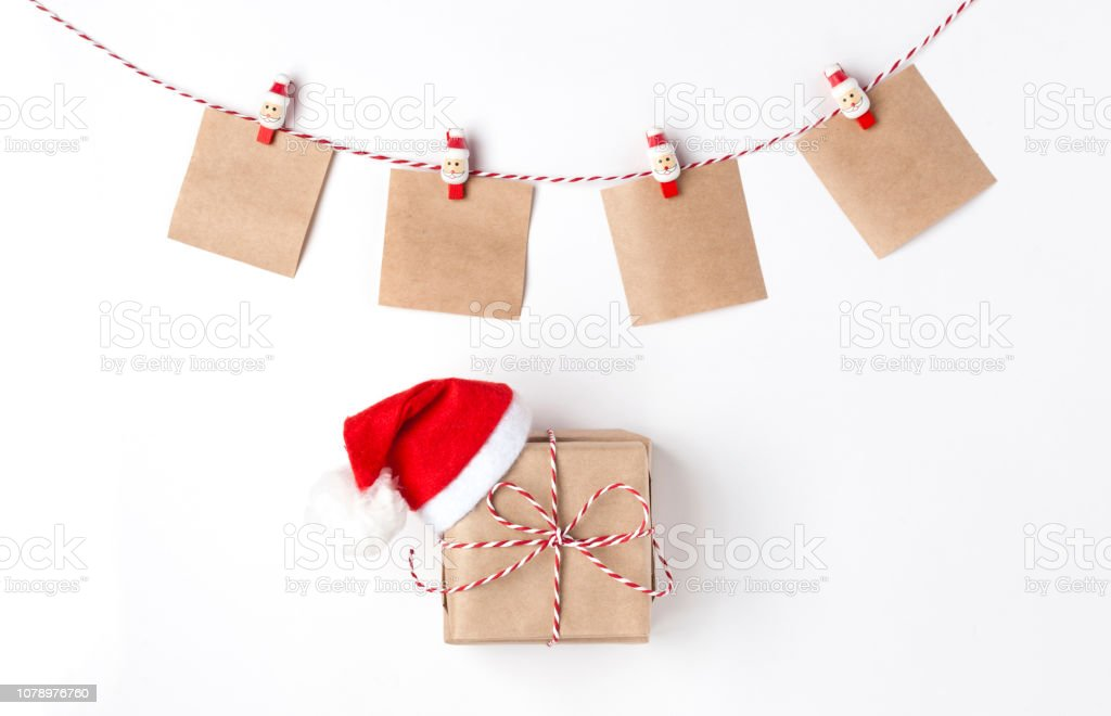 Gift in red hat santa claus, candles, notes with wish on clothespins, Top view White Background Christmas New Year stock photo