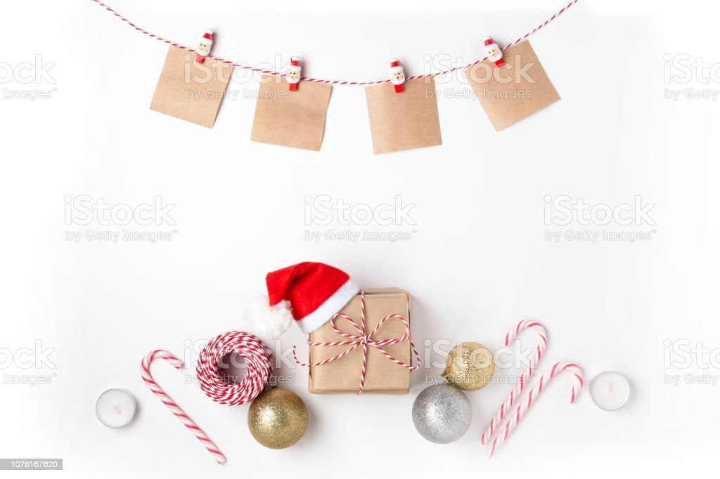 Gift in red hat santa claus, golden and silver balls, candles, notes with wish on clothespins, Top view White Background Christmas New Year stock photo