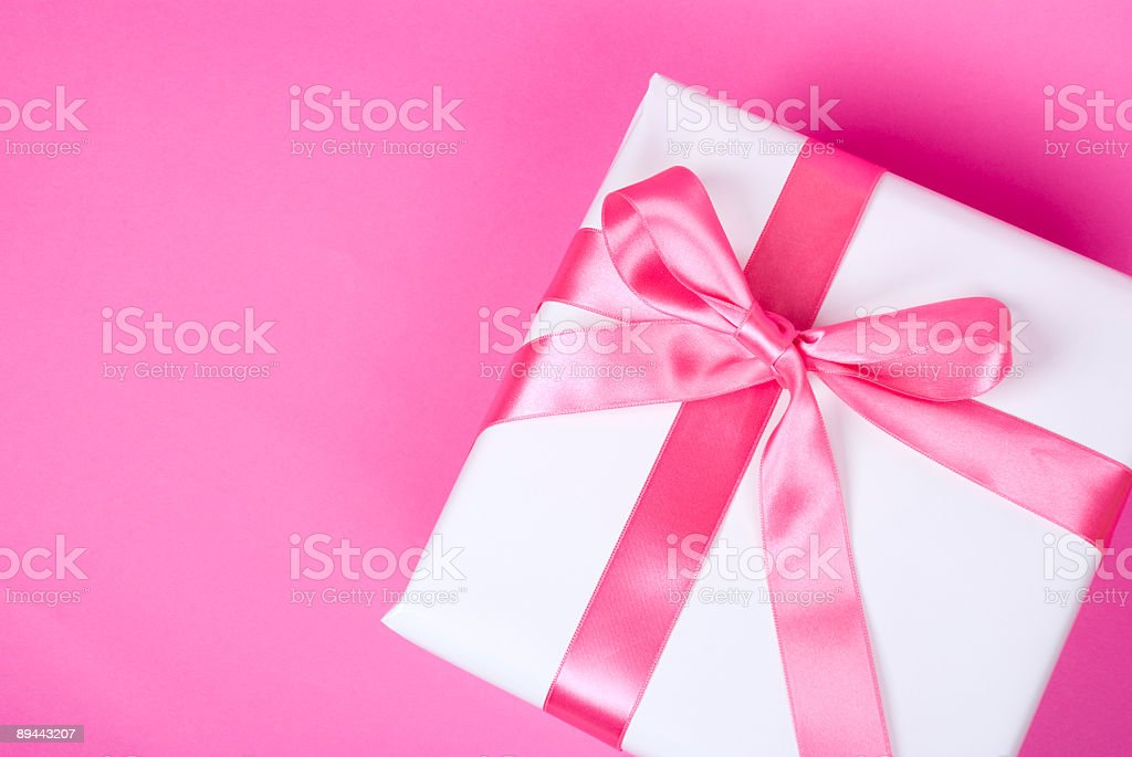 Gift in white wrapping with pink bow against pink background royalty-free stock photo