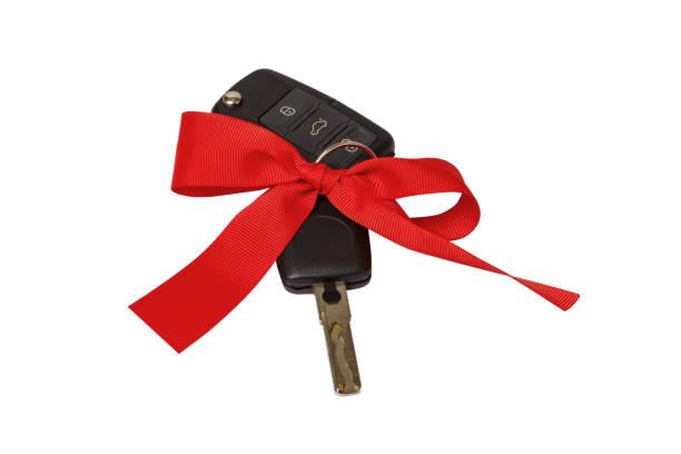 schlüsselbegriff geschenk mit roter schleife auf weißem hintergrund - autoschleifen stock-fotos und bilder