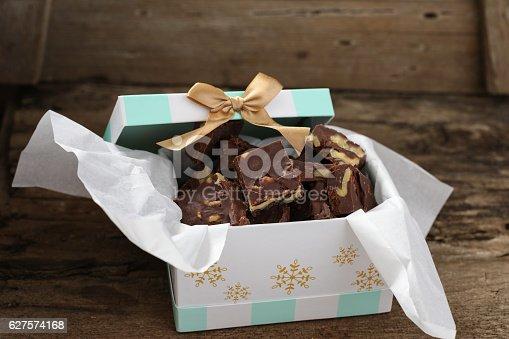 A high angle close up horizontal photograph of a cardboard gift box full of homemade chocolate fudge squares.