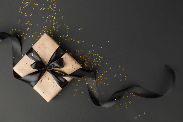 geschenk oder geschenk-box und gold sterne konfetti auf schwarzetisch-top-ansicht. flache laien zusammensetzung für geburtstag, muttertag, schwarzen freitag verkauf, weihnachten, weihnachten, neue yaer oder hochzeit. - gutschein weihnachten stock-fotos und bilder