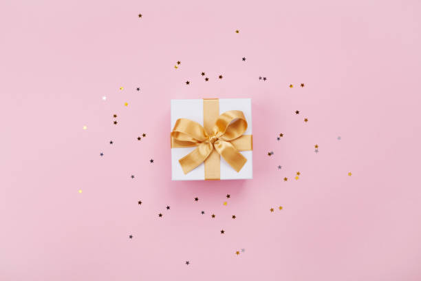Gift or present box and stars confetti on pink pastel table top view. Flat lay composition for birthday, mother day or wedding. Gift or present box and stars confetti on pink pastel table top view. Flat lay composition for birthday, mother day or wedding. Copy space for text. gift box stock pictures, royalty-free photos & images